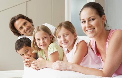 Una familia tradicional joven con tres hijos, mira sonriente.